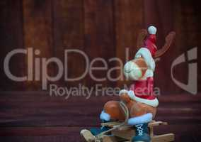 Christmas toy deer in formal attire sitting on a sledge, a brown