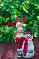 Christmas reindeer with snowman toy on blurred green background