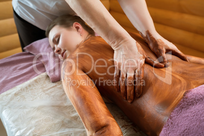 Chocolate massage. Close-up of masseur's hands