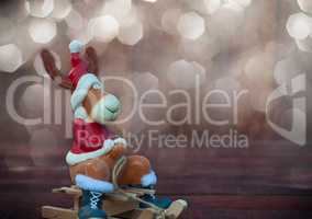 Christmas toy deer in formal attire sitting on a sledge