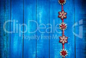 Ribbon with felt snowflakes on a blue wooden surface, copy space
