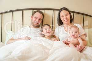 Mixed Race Chinese and Caucasian Baby Boys Laying In Bed with Th