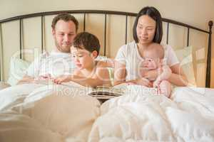 Chinese and Caucasian Baby Boys Reading a Book In Bed with Their