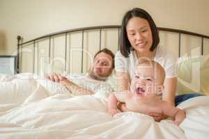 Chinese and Caucasian Baby Boy Laying In Bed with His Parents