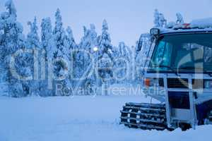Winter Evening and the Snowcat on the Edge of the Forest