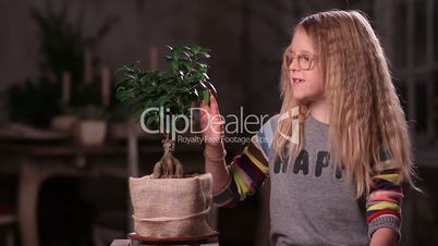 Little girl taking care of green plant