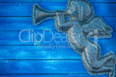 Figure angel of shiny particles on a blue wooden background