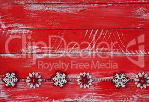 Garland with felt snowflakes on red shabby wooden surface