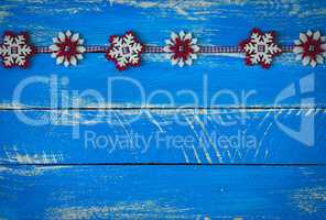 felt snowflakes on a blue wooden surface