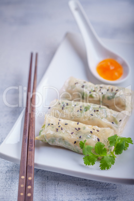 Spring Rolls with Sauce on a wooden surface