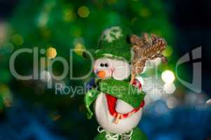 Christmas snowman on the background of blurred lights green tree