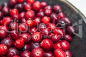 Fresh cranberries fruits in rustic wooden bowl in daylight