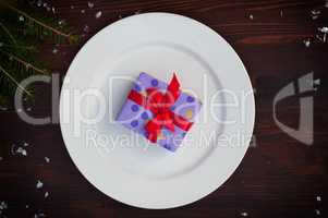 Packed gift with a red ribbon on a white plate