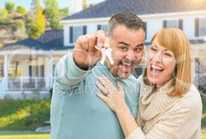 Happy Mixed Race Couple in Front of House with New Keys