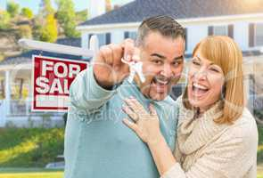 Mixed Race Couple With Keys in Front of Real Estate Sign and New