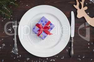 Packed gift on white empty plate, brown vintage in a festive tab