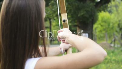 Girl stretches arrow for the bow and aim at the target, close up from behind
