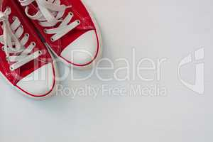 pair of red sneakers youth on a white wooden surface