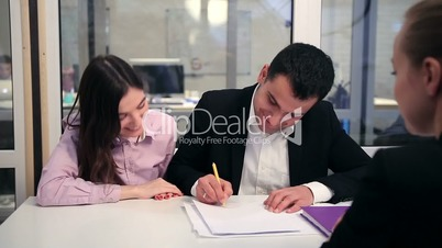 Happy couple signing real-estate contract