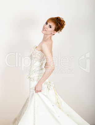 Beautiful young redhead bride wearing white wedding dress with professional make-up and hairstyle