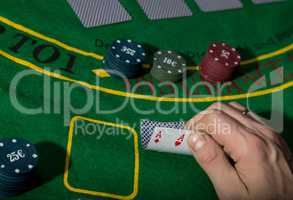 poker playing card on a green table background, man holding two aces