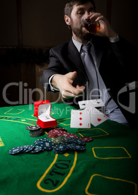 gambling addiction. man in a business suit drinking brandy and throws cards with losing combination. casino chips, precious ring on green poker table