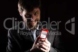 bearded man in business suit gives a ring in the red box and expresses different emotions on dark background