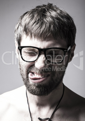 bearded man in glasses plays the fool. crazy boy, funny expression
