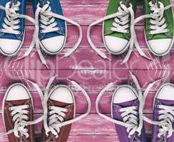 Youth colored sneakers on old pink wooden surface, top view