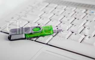 Laptop and green usb memory stick