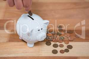 Hand inserting a coin into the piggy bank