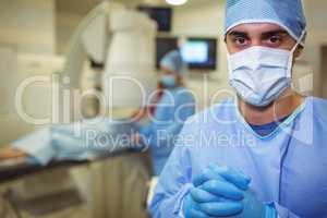 Portrait of male surgeon standing in operation theater
