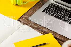 Laptop, diary, pen, coffee mug and headphones