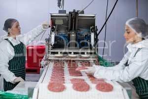 Female butcher processing hamburger patty