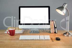 Books, table lamp and desktop pc on table