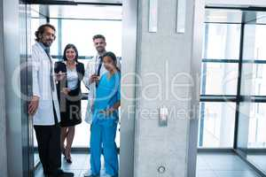 Doctors and businesswoman standing in elevator