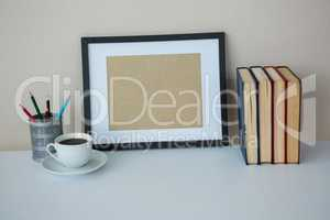 Books with picture frame and a cup of coffee