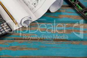 Paper scrolls, pencil, calculator and spirit level
