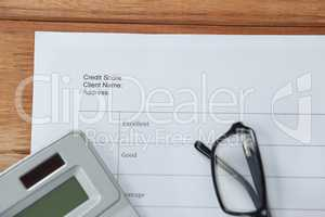 Paper document with calculator and spectacles