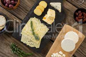 Variety of cheese, olives, biscuits and rosemary herbs on wooden table