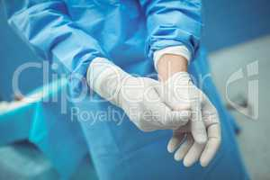 Male surgeon removing surgical gloves in operation theater