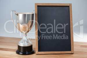 Trophy and chalkboard on wooden table