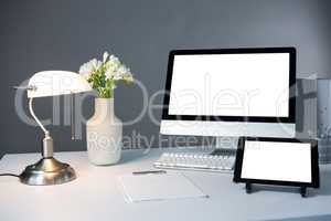 Desktop pc, digital tablet and table lamp with flower vase on table