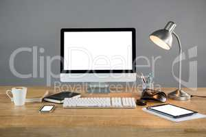 Desktop pc, digital tablet and table lamp with office accessories