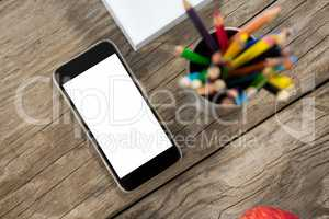 Smartphone and color pencils on wooden table