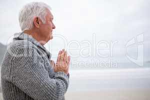 Senior man rubbing hands on beach