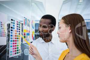 Graphic designers looking at color chart
