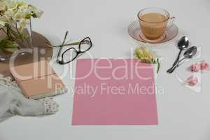 Cup of tea, spoons, spectacles, diary, cloth, blank page, paper balls and flowers
