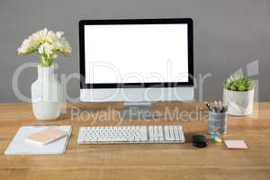 Desktop pc, flower vase and office stationery