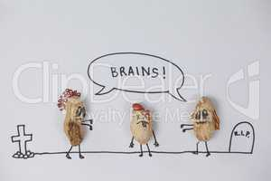 Two zombie  figurines getting tempted towards the brain of  broken head figurine